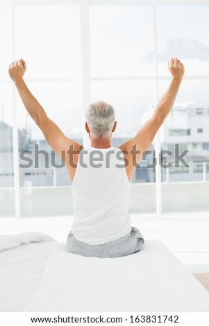 Rear view of a mature man waking up in bed and stretching his arms