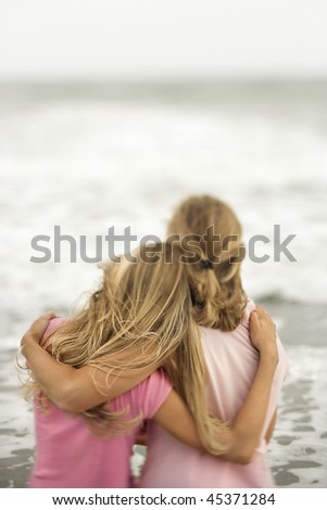 Rear view of a mother and daughter embracing at the beach. Vertical shot. - stock photo