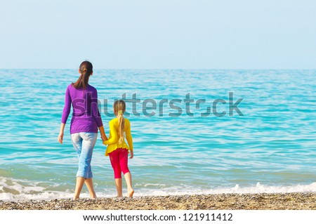 Rear view of a mother and teenage daughter standing on the beach