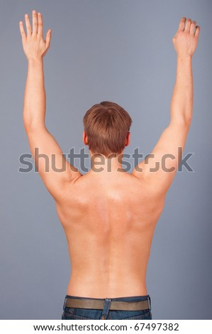 Rear view of a muscular young man with his arms raised - stock photo