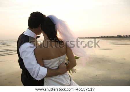 Rear view of a newlywed couple hugging on beach. Horizontal shot. - stock photo