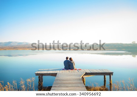 Rear view of a romantic young couple sitting on the pier enjoying beautiful lake.