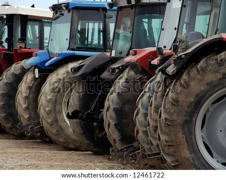 Rear view of a row of powerful agricultural tractors with mud. - stock photo