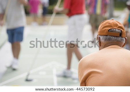 Rear view of a senior man playing shuffleboard - stock photo