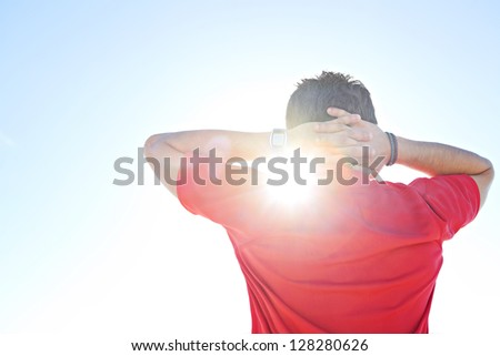 Rear view of a sports man wearing a red shirt with his hands interlinked behind his head, against a deep blue sky with sun rays filtering through his neck. - stock photo
