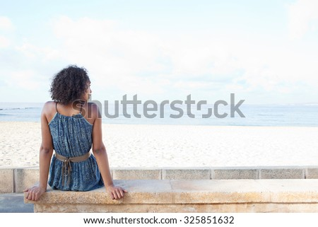 Rear view of a stylish african american young woman sitting by white sand beach contemplating the sea on a sunny summer holiday destination, outdoors. Travel lifestyle and healthy living, exterior. - stock photo