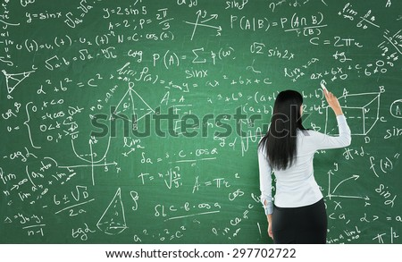 Rear view of a thoughtful woman who is writing math calculations on green chalk board. - stock photo