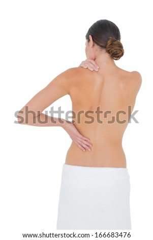 Rear view of a topless fit young woman with shoulder pain over white background
