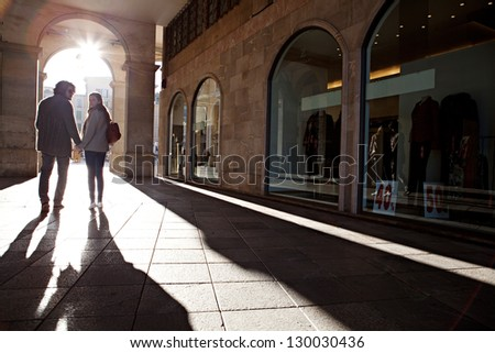 Rear view of a tourist couple silhouette holding hands and turning while on vacation, walking under an old arch with the morning sun rays filtering through. - stock photo