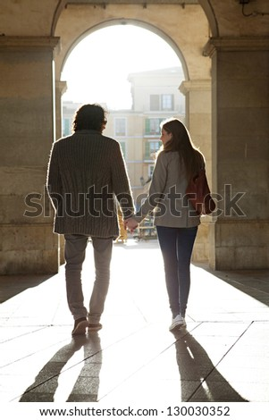 Rear view of a tourist couple silhouette holding hands while visiting a destination city, walking under an old arch with the morning sun rays filtering through.