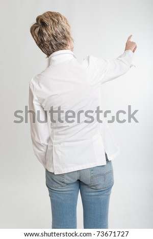 Rear view of a woman pointing at something or dialing
