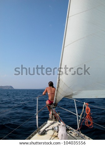 Rear view of a woman sitting on the bow of the yacht with blue sea in background - stock photo