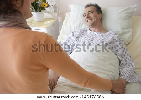 Rear view of a woman visiting man in hospital - stock photo