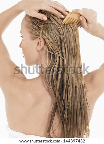 Rear view of a young blond woman combing her wet hair against white background - stock photo