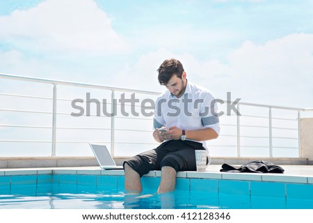 Rear view of a young business man with a briefcase looking at the blue sky - stock photo
