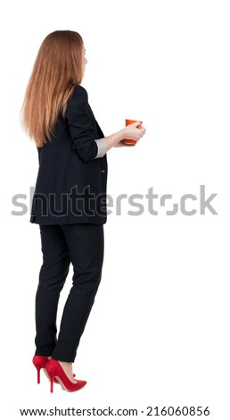 Rear view of a young business woman drinking coffee or tea while relaxing.  Young girl in suit.  Rear view people collection.  backside view of person.  Isolated over white background. - stock photo