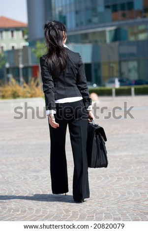 rear view of a young business woman going to the office