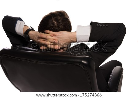 Rear view of a young Caucasian relaxed businessman sitting in a comfortable leather office chair, with the hands clasped behind his head, on white background - stock photo