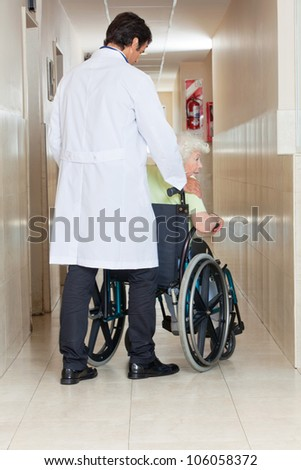 Rear view of a young doctor with senior woman sitting in wheel chair at hospital corridor - stock photo