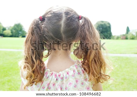 Rear view of a young girl's ponytails standing in the park. - stock photo