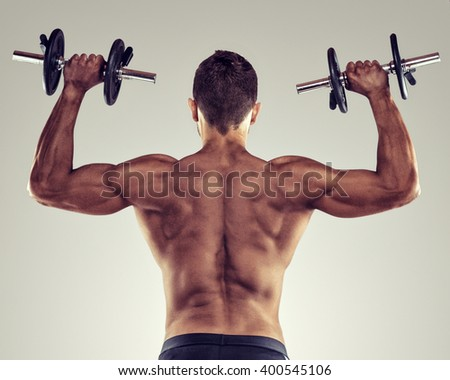 Rear view of a young male bodybuilder doing heavy weight exercise with dumbbells.  - stock photo