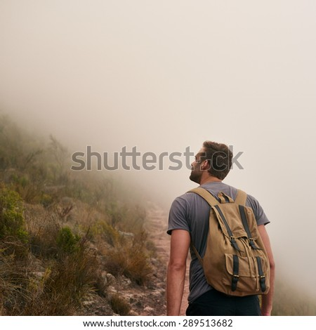 Rear view of a young man on a mountain path looking up on a misty morning - stock photo