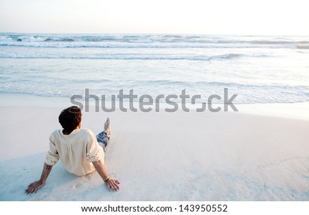 Rear view of a young man sitting on a white sand beach during sunset contemplating the scenery and the blue sea waves during his vacation in an idyllic nature scene destination. - stock photo