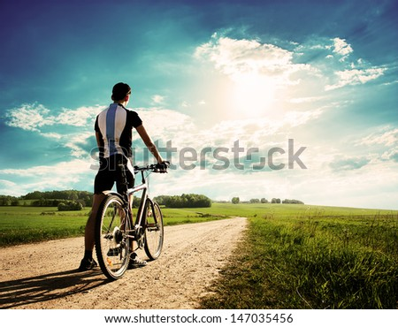 Rear View of a Young Man With Bicycle on Summer Nature Background. Healthy Lifestyle Concept. Copyspace. - stock photo