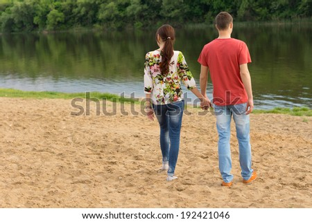Rear view of a young romantic couple wearing blue jeans and holding hands while walking towards the edge of a lake with ripples and reflections of the green foliage, in a warm summer day - stock photo