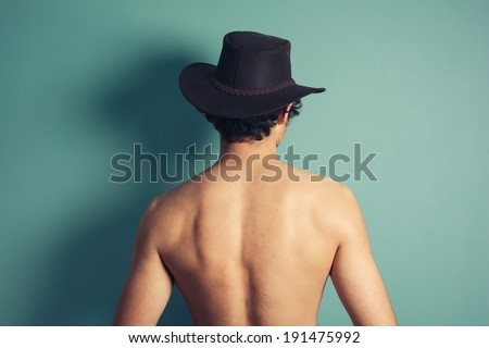 Rear view of a young shirtless man wearing a cowboy hat - stock photo