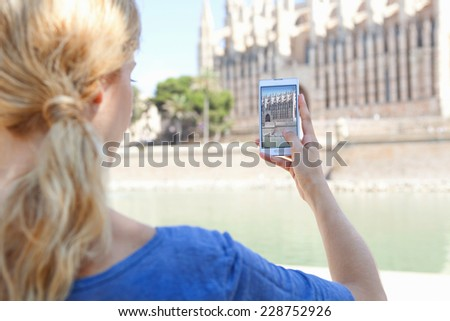 Rear view of a young tourist woman using a smartphone device to take a picture of a cathedral, visiting a destination city on vacation. Holiday maker using technology taking photos on a sunny day. - stock photo