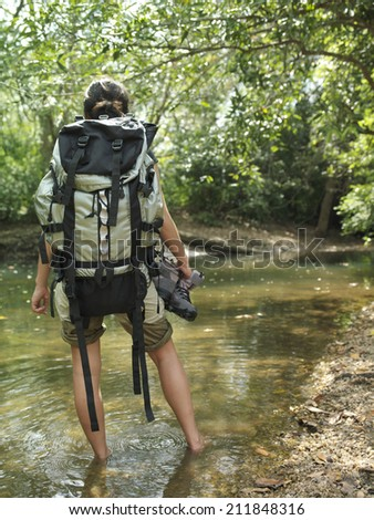 Rear view of a young woman carrying backpack while walking in forest water - stock photo