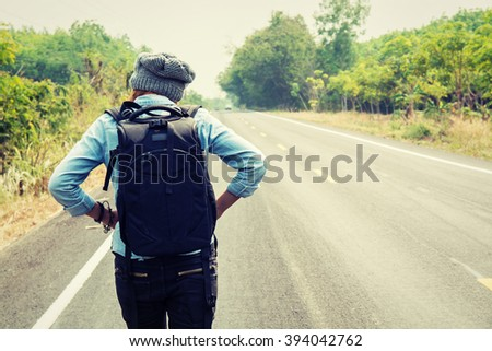Rear view of a young woman hitchhiking carrying backpack walking on the road - stock photo