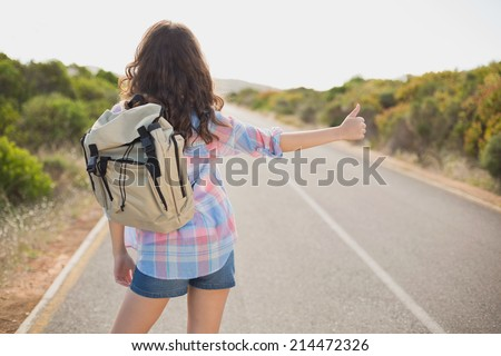 Rear view of a young woman hitchhiking on countryside road - stock photo