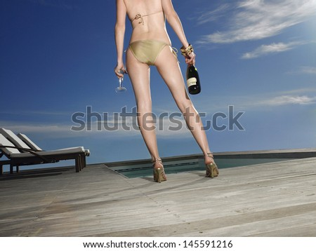 Rear view of a young woman in bathing suit holding champagne bottle at poolside - stock photo