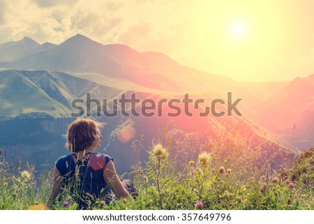 Rear view of a young woman sitting at the top of a mountain, looking into the distance on the top of mountain. Background is mountains and cloudy sky. - stock photo