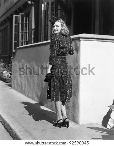 Rear view of a young woman standing in front of a wall looking over her shoulder - stock photo