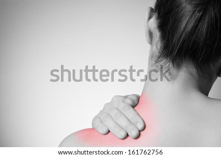 Rear view of a young woman touching her back - stock photo