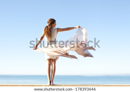 Rear view of a young woman wearing a silk dress and rising a floating sarong up with her arms against a bright blue sky and sea on a holiday beach, outdoors. Travel and healthy lifestyle. - stock photo