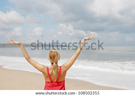 Rear view of a young woman with her arms outstretched in the air while standing by the shore on a golden sand beach.