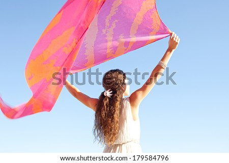 Rear view of a young woman with her arms up in the air holding a pink silk fabric floating with the breeze during a sunny summer day on holiday, against a bright blue sky. Outdoors beauty lifestyle. - stock photo