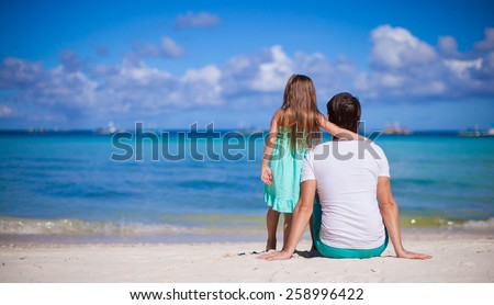 Rear view of Adorable little girl and young dad at tropical beach - stock photo
