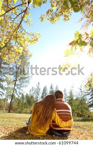 Rear view of affectionate couple relaxing outdoors in autumn - stock photo