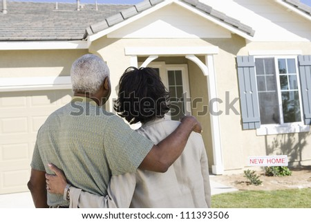Rear view of African American couple standing in front of new house - stock photo