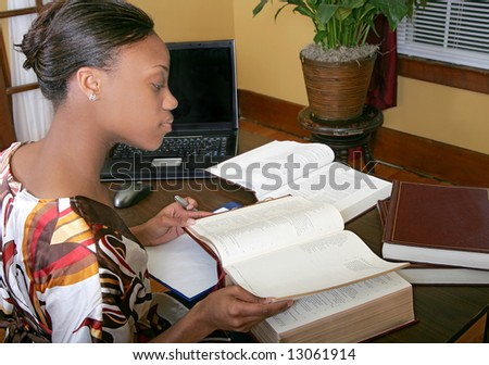 rear view of African American female business woman working with books at a laptop computer
