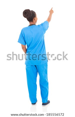 rear view of african american nurse pointing empty space - stock photo