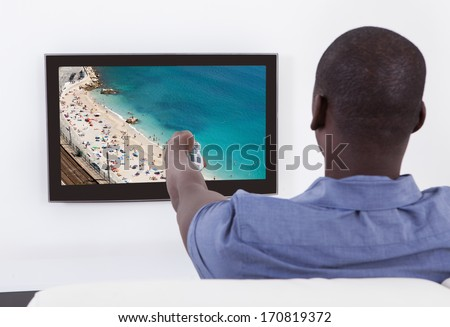 Rear View Of African Man Changing Channel With Remote