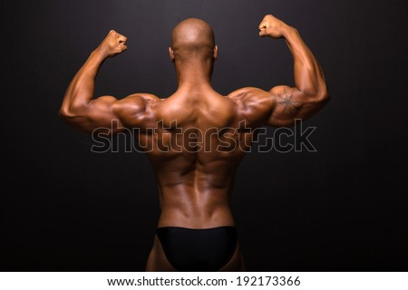 rear view of afro american male bodybuilder posing on black background