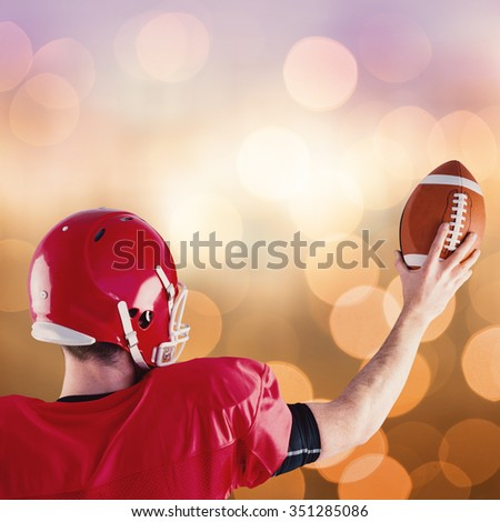 Rear view of american football player holding up football against blue glowing background