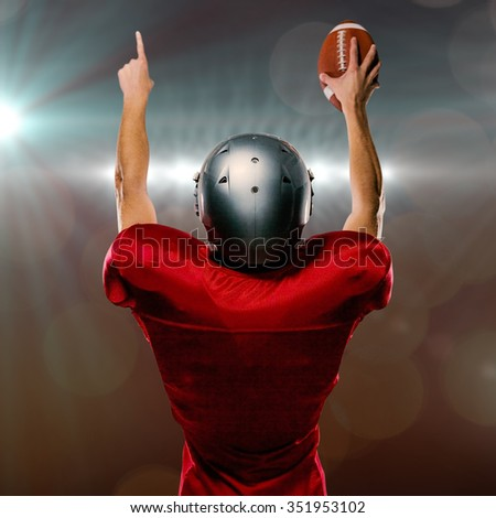 Rear view of American football player with arms raised against spotlights - stock photo